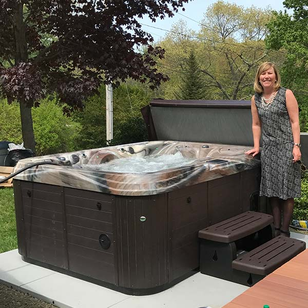 woman standing next to her new hot tub