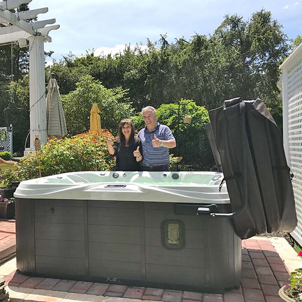 couple with thumbs up in front of new hot tub
