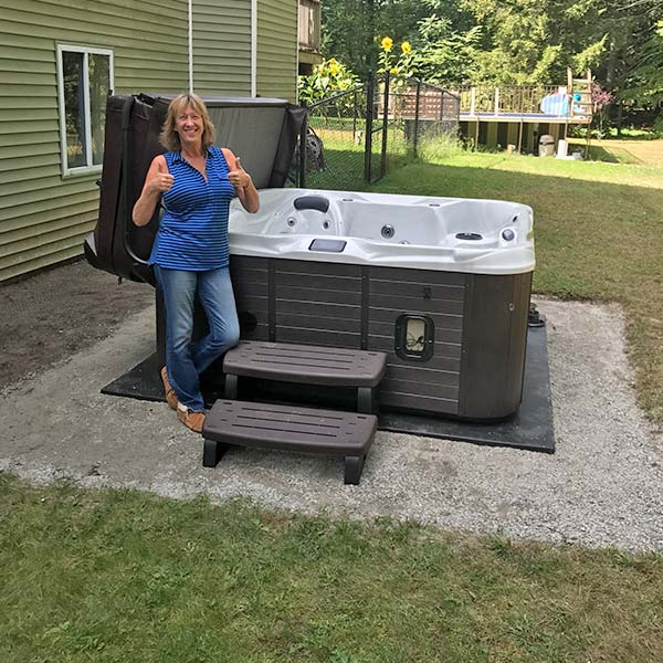 woman holding a thumbs up in front of new hot tub