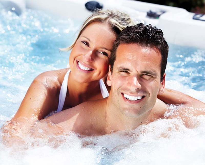 smiling couple in a hot tub