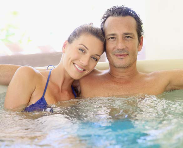 couple sitting in a hot tub smiling