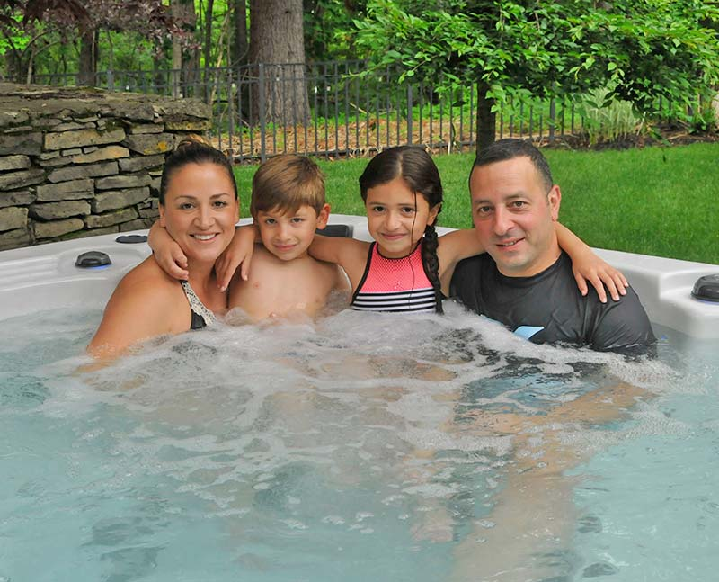 family smiling in a hot tub