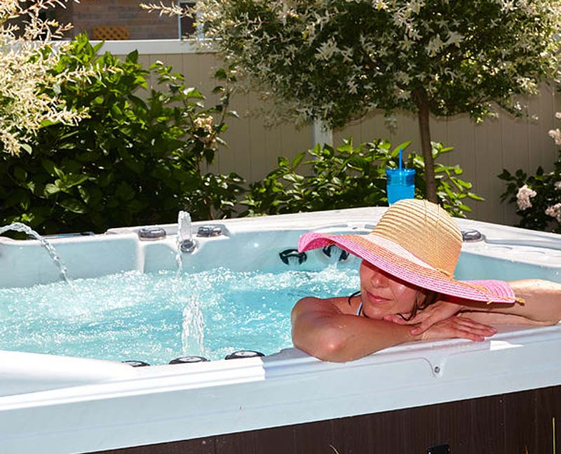 woman with hat lounging in hot tub